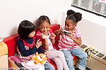 Education preschool 3-4 year olds pretend play group sitting on sofa playing and talking one girl pretending to take pictures with small camera horizontal
