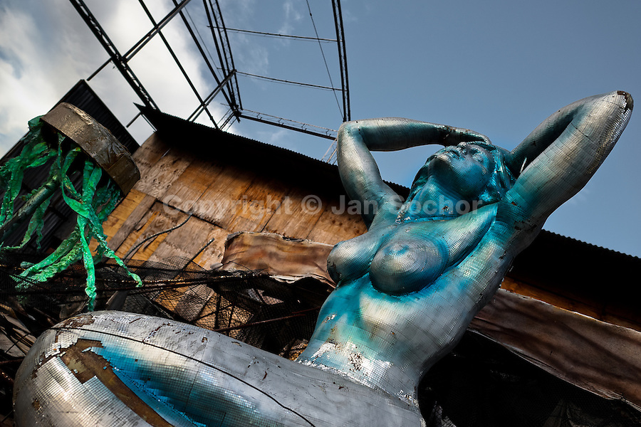 A damaged carnival statue of a mermaid abandoned on the work yard behind the Samba school workshops in Rio de Janeiro, Brazil, 15 February 2012. Most of the large carnival floats, colorful designs and fancy costumes are dismantled, cut into pieces or simply thrown into garbage right after the last day of the Carnival. The low-tech materials as fiberglass, plastic or polystyrene, which most of the of the carnival floats and statues are made of, are stocked in the warehouses to be recycled and used in the future parades. However, there is no use for some of the statues so they slowly fall apart into pieces forming a ?Carnival cemetery? in the industrial yards around the port of Rio de Janeiro.