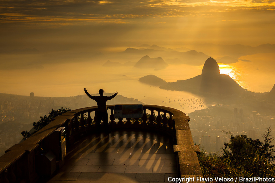 """Sunrise in Rio de Janeiro, Brazil. Sugar Loaf Mountain from the Christ the Redeemer statue point of view. Rio de Janeiro is on a strip of Brazil's Atlantic coast, close to the Tropic of Capricorn, where the shoreline is oriented east-west. Facing largely south, the city was founded on an inlet of this stretch of the coast, Guanabara Bay (Baía de Guanabara), and its entrance is marked by a point of land called Sugar Loaf (Pão de Açúcar)?a """"calling card"""" of the city. Rio de Janeiro is one of the most visited cities in the southern hemisphere and is known for its natural settings."""