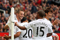 Pictured: Gylfi Sigurdsson of Swansea (L) with team mates celebrating his goal, making the score 2-1 to his team. Saturday 16 August 2014<br />