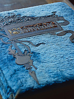 A book bound with blue velvet bears an engraved, metal panel delicately nailed to the front
