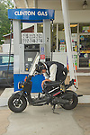 Clinton Gas, CT. Elderly man with scooter filling gas tank.