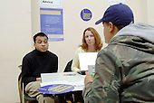 Residents talk with citizens advice bureau staff and jobs, benefits and banking advisors at an open day at the Beethoven Centre, Queens Park, London.