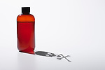 Bottle with poisonous liquid and skull and crossbones shadow, studio shot