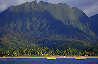 Hanalei Bay's Na Molokama mountain, with Hawaiian canoe paddlers off Hanalei Beach, North Shore, Kauai, Hawaii