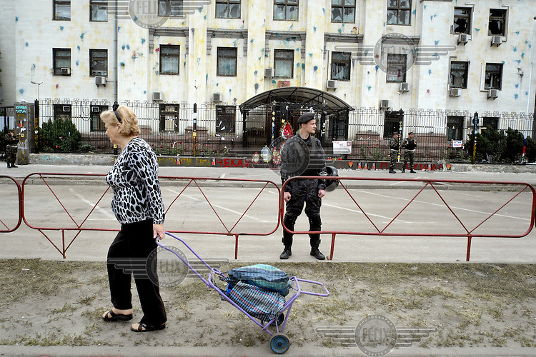 A woman walks by the heavily protected Russian Embassy. On 14 June 2014 several hundred hundred protesters, angry at the deaths of 49 Ukrainian soldiers near Luhansk, converged on the embassy, overturned several diplomatic cars and piled up tyres to block entry into building. They also threw rocks, smoke grenades, eggs and paint at the premises.