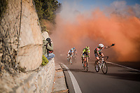 It's not clear whether Mirco Maestri (ITA/Bardiani - CSF) condemns or is greeting the tifosi's resposible for the smoke up the Capo Berta<br /> <br /> thik smoke once again covers the Capo Berta passage of the riders > but this time year the bushes catch fire (!! 🔥) and flair up just as the riders ride by<br /> <br /> 110th Milano-Sanremo 2019 (ITA)<br /> One day race from Milano to Sanremo (291km)<br /> <br /> ©kramon