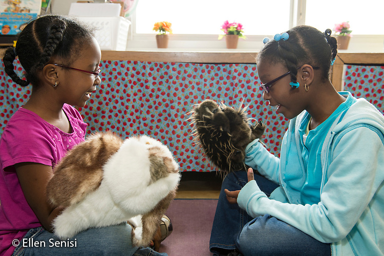 MR / Schenectady, New York. Yates Arts-in-Education Magnet School (urban public school). First grade classroom. Students engaged in imaginary play with puppets during free playtime. Left: girl, 6, African American; Right: girl, 6. MR: Wil40, Cov1. ID: AM-g1w. © Ellen B. Senisi.
