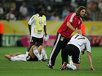 German teammate Torsten Frings lays a comforting hand on defender (17) Per Mertesacker.  Italy defeated Germany, 2-0, in overtime in their FIFA World Cup semifinal match at FIFA World Cup Stadium in Dortmund, Germany, July 4, 2006.