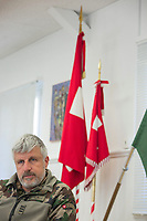 """Switzerland. Canton Ticino. Rivera. Colonel Nicola Guerini is the commanding officer of Monte Ceneri military base. He is also the military chief of the Special Forces Command (German: Kommando Spezialkräfte), an infantry corps of the Swiss Armed Forces specialised in rapid offensive operations, intel gathering and operations in urban areas, open fields and other difficult terrains, capable of acting on short notice. In his office, the professional soldier seats close to Swiss and Special Forces Command flags. Due to the spread of the coronavirus (also called Covid-19), the Federal Council has categorised the situation in the country as """"extraordinary"""". The army was called upon to provide logistical support and to offer its skills in terms of medical assistance (ambulances, field hospital, tents, nurses,..). The militia soldiers from medical troops were called by the Swiss army for the first time since World War II. Under the country's militia system, professional soldiers constitute a small part of the military and the rest are conscripts or volunteers aged 19 to 34 (in some cases up to 50). Monte Ceneri is a mountain pass in the canton of Ticino. It connects the Magadino plain and the Vedeggio valley across the Prealps. 2.04.2020 © 2020 Didier Ruef"""