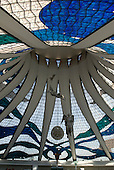 Brasilia, Brazil. Interior of the Metropolitan Cathedral of Our Lady (Catedral Metropolitana Nossa Senhora Aparecida), by architect Oscar Niemeyer. The cathedral is an iconic landmark on the Ministries Esplanade. Inside it has flying angels and beautiful stained glass.