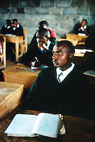 Kenya. Rift Valley Province. Nyahururu. Classroom at Munyaka secondary school. A student listens to his teacher's lesson.His notebook is laid on a wood desk . The boy is wearing a green uniform and a tie. © 2004 Didier Ruef