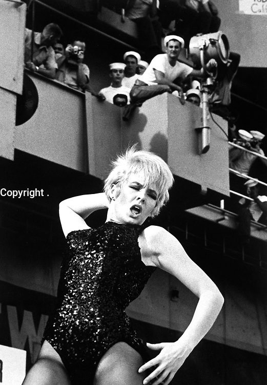 """Watusi, Frug, Shimmy, Twist!  On a carrier? - It's swinging time on board Ticonderoga as Miss Joey Heatherton rocks out with a """"Tico Tiger"""" during the Bob Hope Show.  (USIA)<br /> NARA FILE #:  306-MVP-8-6<br /> WAR & CONFLICT BOOK #:  391"""