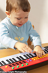 Two year old toddler boy playing with electronic piano keyboard hitting keys and buttons