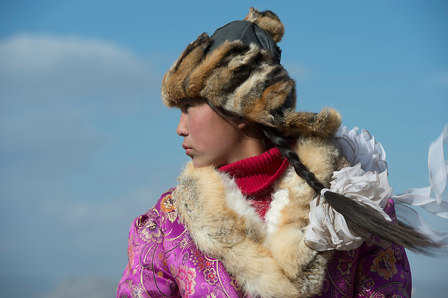 Portrait of a Kazakh teenage girl eagle hunter at the Golden Eagle Festival on the festival grounds near the city of Ulgii (Ölgii) in the Bayan-Ulgii Province in western Mongolia.