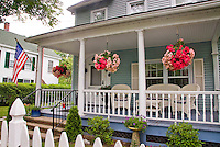 Hanging baskets of begonias on front porch of prety Colonial house painted blue, with American flag, white picket fence, wicker furniture, plants