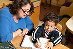 Education preschool 3-4 year olds female teacher working with boy art activity drawing listening to him horizontal