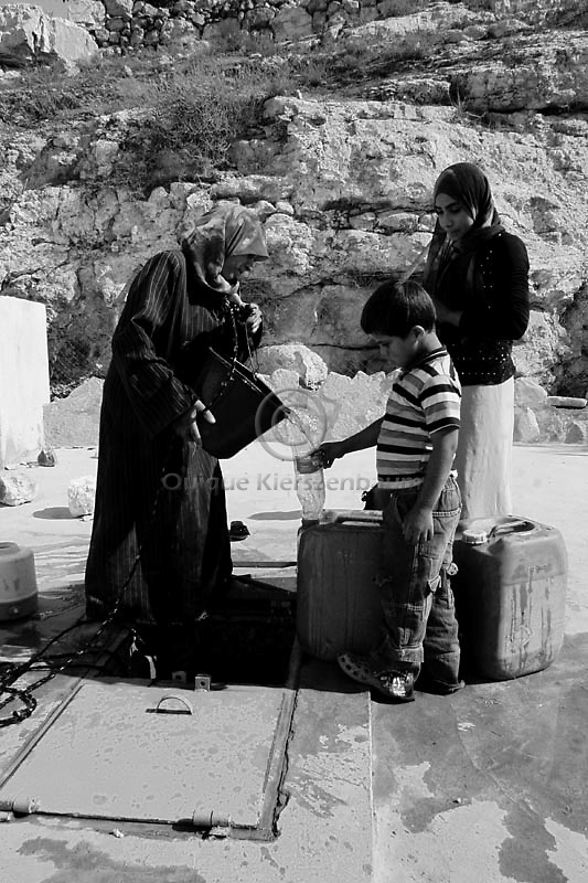Palestinian women fill containers of water at a local well in the Palestinian village of Twani, in the West Bank. The water crisis has increased in the West Bank in the last months due the Israeli restrictions on water. Amnesty International has accused Israel of denying Palestinians adequate access to water while allowing Jewish settlers in the occupied West Bank almost unlimited supplies. Photo by Quique Kierszenbaum