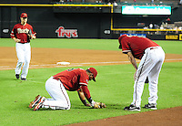 Jun. 1, 2011; Phoenix, AZ, USA; Arizona Diamondbacks pitcher Daniel Hudson (right) checks on first baseman Juan Miranda after they collided attempting to catch a foul pop in the third inning against the Florida Marlins at Chase Field. Mandatory Credit: Mark J. Rebilas-