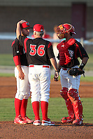 Batavia Muckdogs pitching coach Ace Adams talks with pitcher Andy Moss and catcher Roberto Espinoza during a game vs. the Lowell Spinners at Dwyer Stadium in Batavia, New York July 16, 2010.   Batavia defeated Lowell 5-4 with a walk off RBI single in the bottom of the 9th inning.  Photo By Mike Janes/Four Seam Images