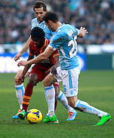 Calcio, Serie A: Lazio vs Roma. Roma, stadio Olimpico, 9 febbraio 2014.<br /> AS Roma forward Gervinho, of Ivory Coast, red jersey, is challenged by Lazio midfielder Senad Lulic, of Bosnia, and defender Stefan Radu, of Romania, right, during the Italian Serie A football match between Lazio and AS Roma at Rome's Olympic stadium, 9 February 2014.<br /> UPDATE IMAGES PRESS/Isabella Bonotto