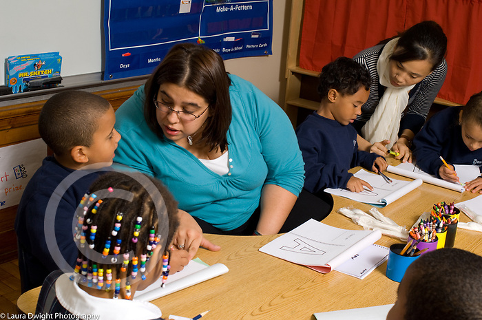 Education Elementary Grades1-2 extra support for student as female teacher works with group