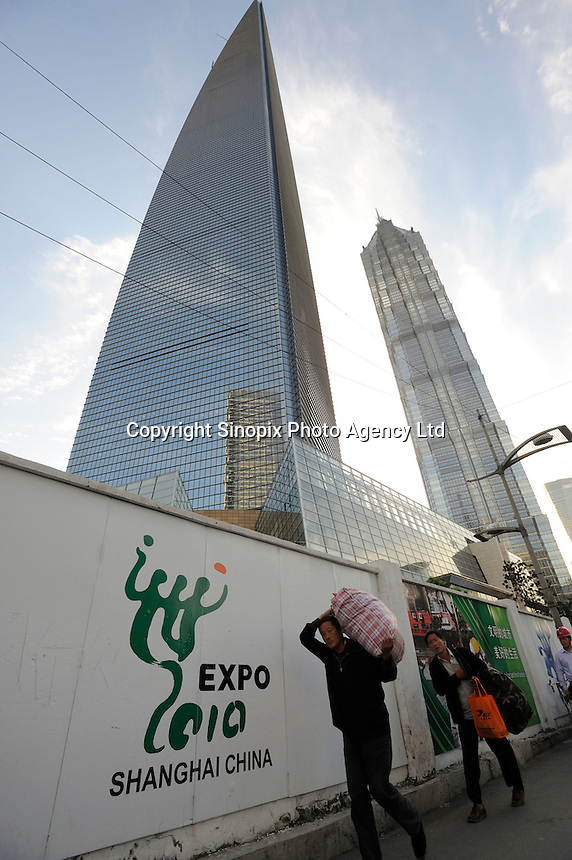 Migrant worker past Expo 2010 sign in front of Jin Mao Tower and the Shanghai World Financial Center in Pudong..14 Oct 2009