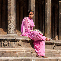 Nepal, Patan.  Nepali Woman with Tika on her Forehead Sitting on Edge of Temple.
