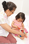 18 month old toddler girl with grandmother, doing peg toy, grandmother steadying toy