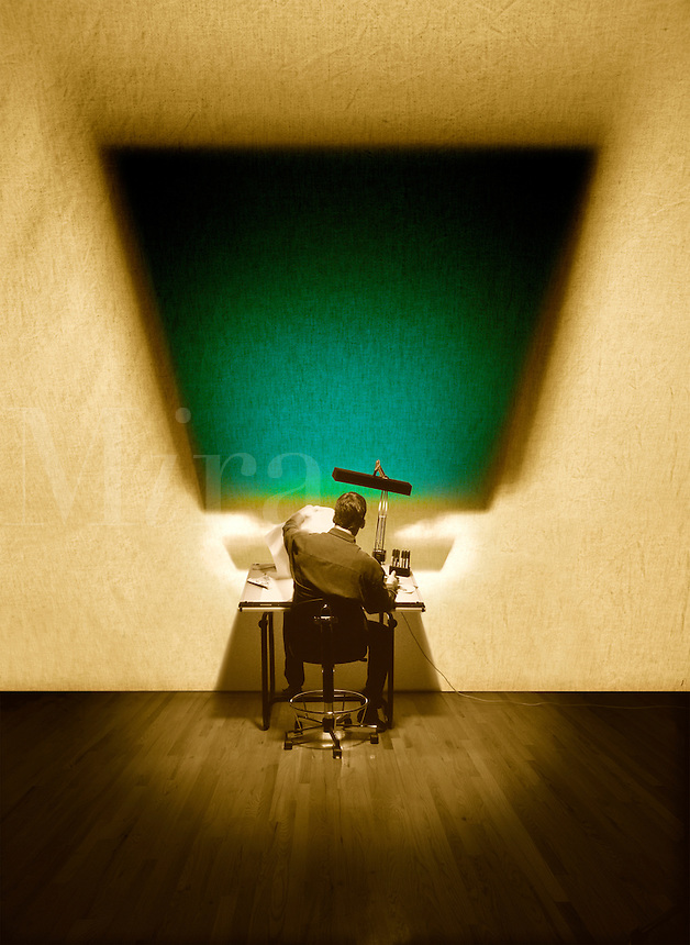 Conceptual photograph where subject is sitting at a drafting table using old technology while a computer and keyboard is a shadow against the wall representing new technology.