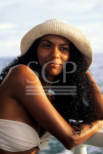 Bahia, Brazil. Smiling young woman with curly black hair in a straw sunhat and white strapless bikini.