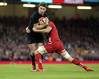 Pictured: Beauden Barrett of New Zealand (with ball) is brought down Saturday 22 November 2014<br />