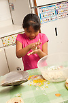 7 year old girl rolling dough for tortilla