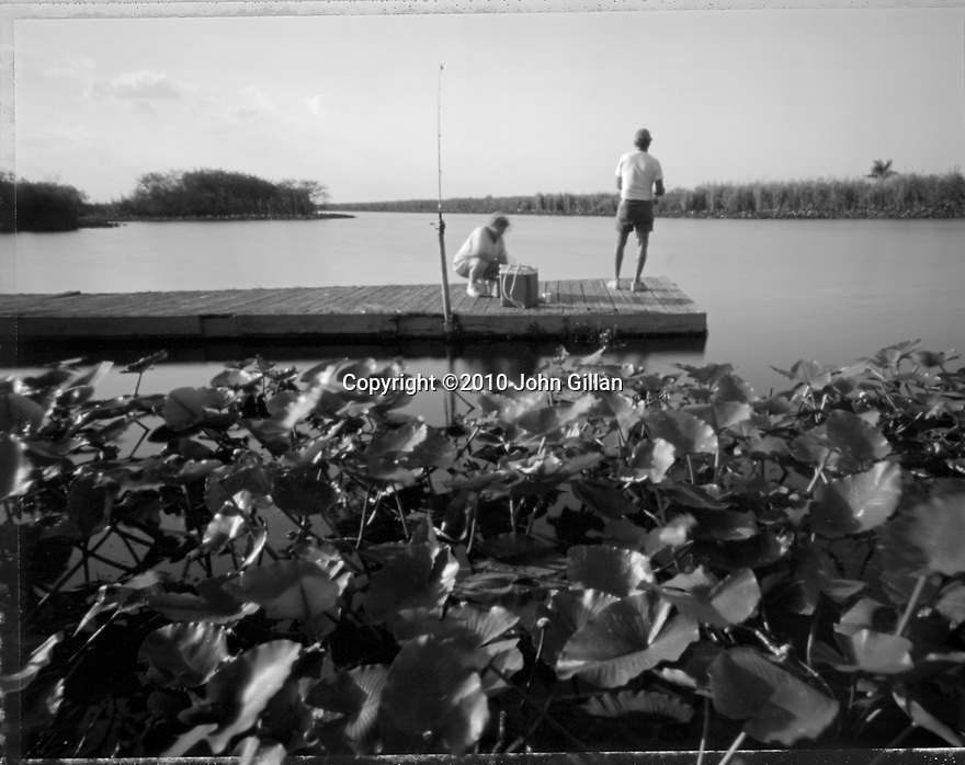 Black and white pinhole photograph of 2 men fishing from a wooden dock in the water at Holiday Park, Florida. Grouping of lily pads in the foreground.