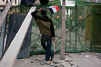 An anti government protester holding an Egyptian flag near a barricade constructed nr Tahrir Square. Throughout Friday, 4 February, anti government protesters protected their positions from pro Mubarak supporters around Tahrir square, the scene of heavy clashes between pro and anti government protesters. Continued anti-government protests take place in Cairo calling for President Mubarak to stand down. After dissolving the government and allowing for talks with opposition parties Mubarak still refuses to step down from power...