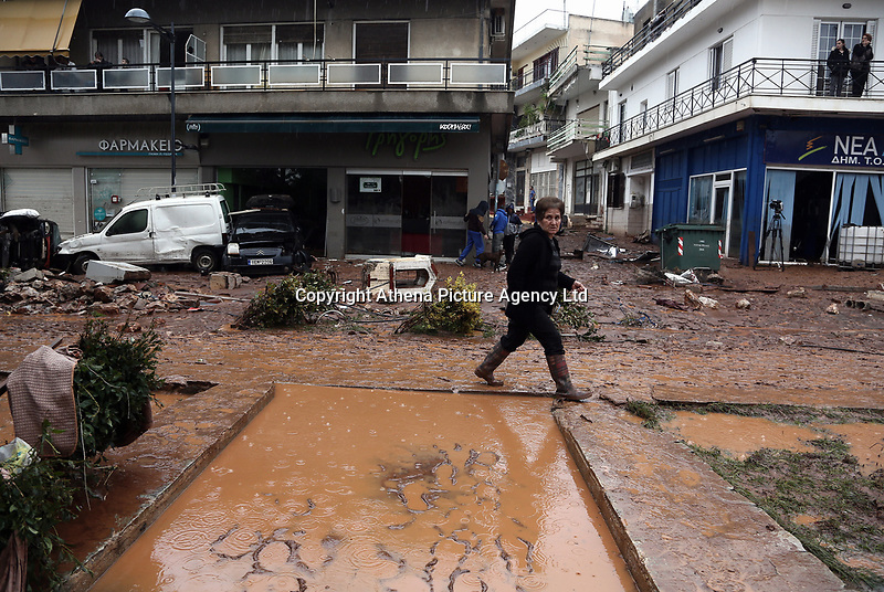 Pictured: A woman walks through mud and debris.<br /> Re: Five people have reportedly died and severe damage caused by heavy rain and flash flooding in the area of Mandra, near Athens, Greece. Wednesday 15 November 2017