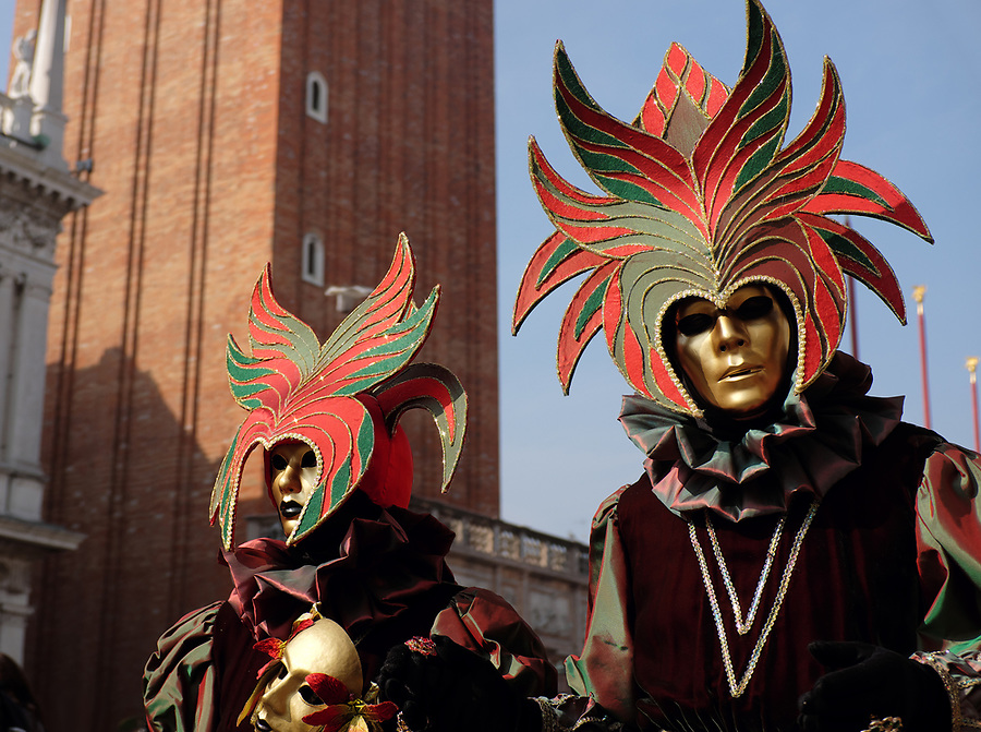 Couple dressed in traditional mask and costume for Venice Carnival standing in Piazza San Marco, Venice, Veneto, Italy