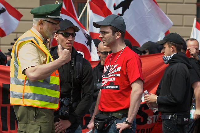 """Etwa 70 bis 80 Neonazis von den Autonomen Nationalisten und der NPD versuchten am Samstag den 14. Mai 2011 in Berlin Kreuzberg eine Demonstration unter dem Motto """"Wahrheit macht frei"""" zu veranstalten. Zu der Demonstration waren Neonazis aus Niedersachsen, Brandenburg und Nordrhein Westfalen angereist. Die Demonstration und die Demonstrationsroute wurde in Zusammenarbeit mit der Polizei geheim vorbereitet. Dennoch gelang es mehr als 800 Menschen die Demonstration mit Blockaden zu verhindern. Die Neonazis wurden von der Polizei in die U-Bahn geleitet, wo sie unter den Augen der Polizei Auslaender verpruegeln konnten.<br /> Im Bild: Der Demonstrationsanmelder Sebastian Schmidtke, Mitglied des sog. """"Nationalen Widerstand Berlin"""" und NPD-Vizelandes-<br /> chef in Berlin (mit rotem T-Shirt) im Gespraech mit der Polizei.<br /> 14.5.2011, Berlin<br /> Foto: Christian-Ditsch.de<br /> [Inhaltsveraendernde Manipulation des Fotos nur nach ausdruecklicher Genehmigung des Fotografen. Vereinbarungen ueber Abtretung von Persoenlichkeitsrechten/Model Release der abgebildeten Person/Personen liegen nicht vor. NO MODEL RELEASE! Don't publish without copyright Christian-Ditsch.de, Veroeffentlichung nur mit Fotografennennung, sowie gegen Honorar, MwSt. und Beleg. Konto:, I N G - D i B a, IBAN DE58500105175400192269, BIC INGDDEFFXXX, Kontakt: post@christian-ditsch.de]"""