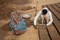 Rajasthan, India.  Husband Turns Brick Mold Over while Wife Prepares Mud for the Next Brick.