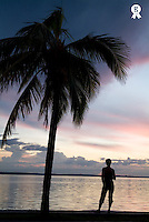 Woman standing under palm tree, looking at sunset over sea  (Licence this image exclusively with Getty: http://www.gettyimages.com/detail/200553557-001 )