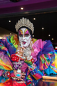 Ipanema, Rio de Janeiro, Brazil. Transvestite with colourful clothes, jewels and makeup, with elaborately decorated fingernails, drinking champagne from a glass during carnival.