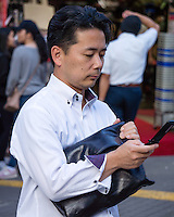 This man is a good representative of an average middle-aged salaryman. He is fashionable, but not extravagant. Summer dress code does not require necktie or jacket for the majority of office workers. Business bag and flip phone are finishing touches.