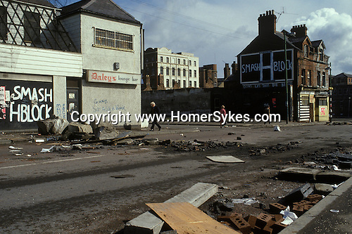 Belfast, Northern Ireland. 1981<br /> Smash the H Block murals decorate the Falls Road a predominately republican Catholic inner city working class enclave. This is the morning after the night before, riot strewn rubble left abandoned after a night of fighting the British army.