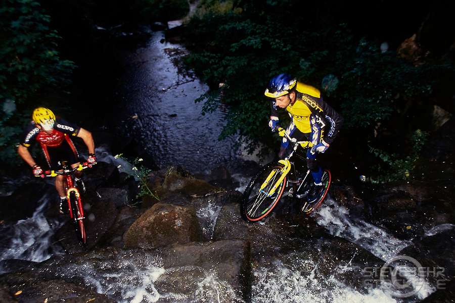 20112-10015-02A Martyn Ashton and Martyn Hawyes riding trials mountain bikes  up a waterfall.  Scott and Volvo Cannondale.  Surrey, Mid 1990's.