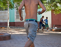 Cuba, Trinidad.  Young Men Playing Soccer (Football) in Park.