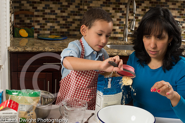 3 year old boy in kitchen at home with mother learning to cook baking, putting cornmeal into bowl
