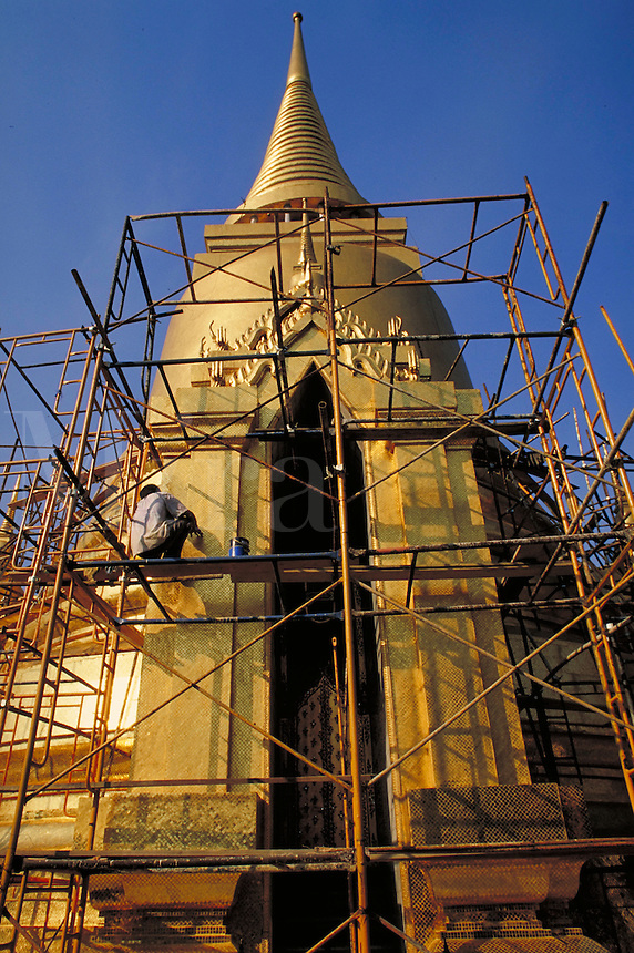 A worker on a scaffold maintains the gold tiled exterior of the Grand Palace. Bangkok, Thailand.