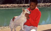 Boy training little dog beside lake, Missouri, USA
