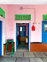 The decorative scheme of the exterior is carried through to the inner courtyard and the interior itself, with pink walls, woodwork painted a bright blue and a decorative frieze in mint green