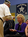 Peggy Eddington-Smith receives her father's replacement dog tags during a ceremony, in Dayton, Nev., on Saturday, Sept. 20, 2013. After 14 years of searching for relatives of World War II Private John F. Eddington, his purple heart medal and other personal items, found in Missouri, were returned to Eddington-Smith. <br /> Photo by Cathleen Allison/Las Vegas Review-Journal